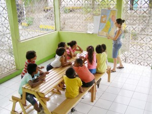 Raquel teaching children on the front patio of their home