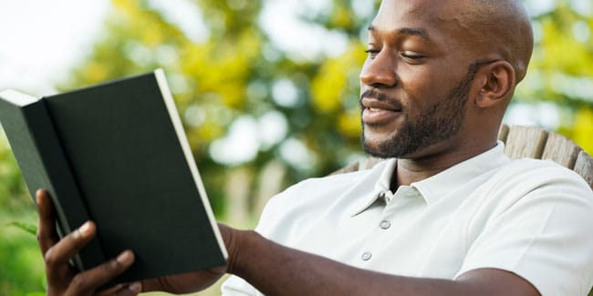 Handsome African American man in his late 20s reading a book at the park on a summer day; Shutterstock ID 151685072; PO: aol; Job: production; Client: drone